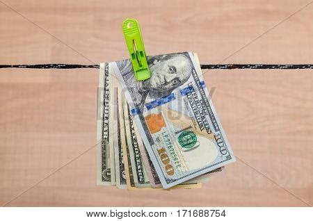 Different dollar bills dry on a cord