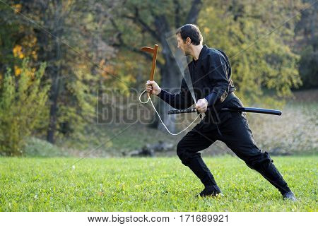 Ninja in black kimono is practicing with kusarigama outdoors in the park.