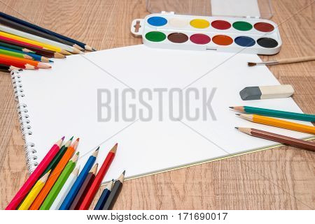 set of colorful paints crayons and brushes with blank album
