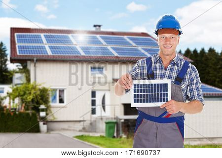 Smiling Repairman Holding Solar Panel In Front Of The House