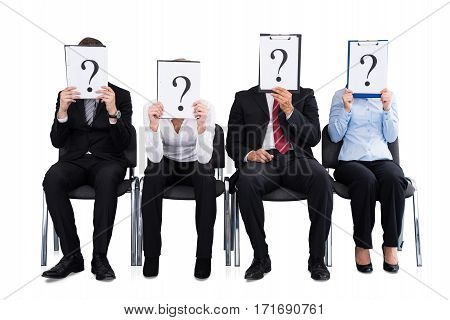 Businesspeople Hiding Their Face Behind A Question Mark Sign On White Background