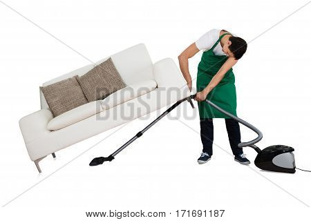 Male Janitor Cleaning Floor With Vacuum Cleaner While Lifting Couch On White Background