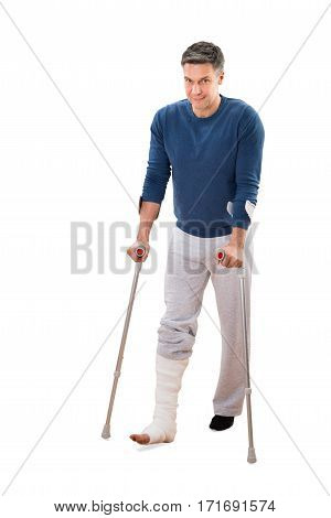 Portrait Of A Disabled Man Using Crutches For Walking On White Background