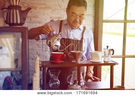 Senior adult man barista making coffee in cafe