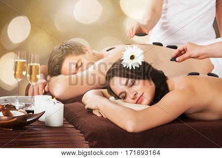 Close-up Of A Relaxed Young Couple Receiving Hot Stone Therapy At Beauty Spa