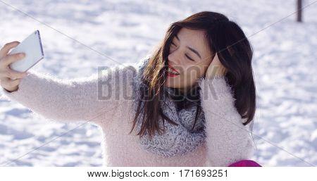 Pretty woman sat on snow taking selfie