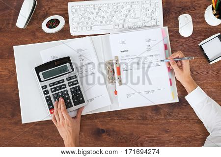 High Angle View Of A Accountant Calculating Invoice Using Calculator At Office