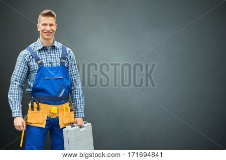 Portrait Of A Happy Male Technician Standing On Gray Background