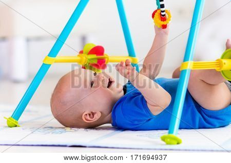 Cute baby boy on colorful playmat and gym playing with hanging rattle toys. Kids activity and play center for early infant development. Newborn child kicking and grabbing toy in white sunny nursery