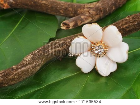 Jewellry ring as flower on green leafs background