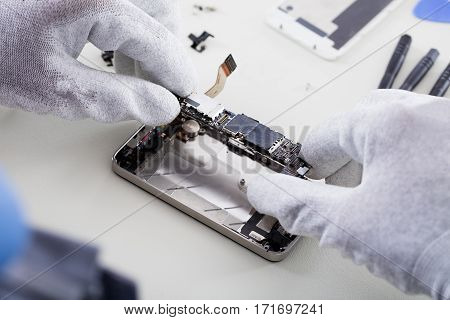 Close-up Of Person's Hand Wearing Glove Repairing Cellphone