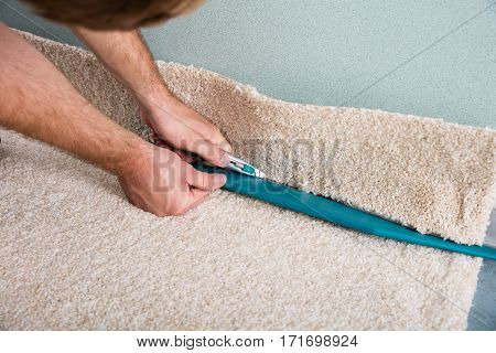 Close-up Of A Craftsman Hands Holding Cutter Cutting Carpet At Home