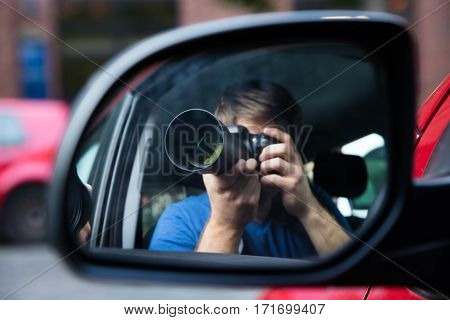 Private Detective Sitting In Car Photographing Reflected In Wing Mirror