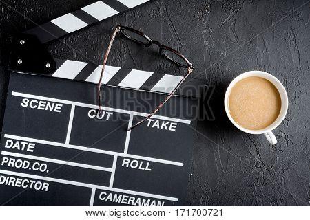 Screenwriter desktop with movie clapper board on dark background top view
