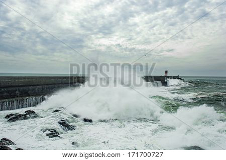 stormy sea waves crushed over pier with lighthouse in Porto Portugal. sea storm
