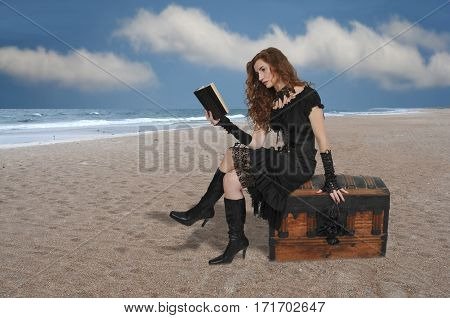 Beautiful young woman pirate reading a book treasure chest
