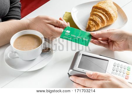 Credit card payment bill in cafe for croissant and coffee on white table background