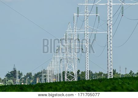 Transmission Tower On A Background Field Of Soybeans
