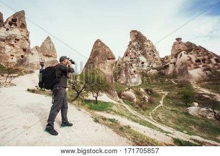 man photographs the ancient city and the castle Uchhysar dug from the mountains. Cappadocia, Turkey