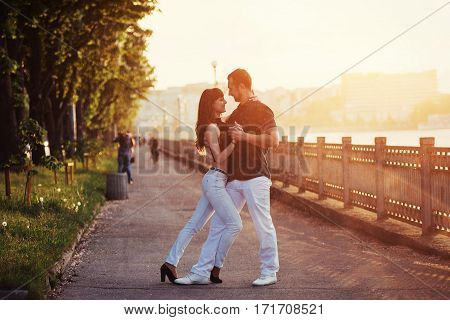 young couple dancing tango on the embankment of the river at sunset