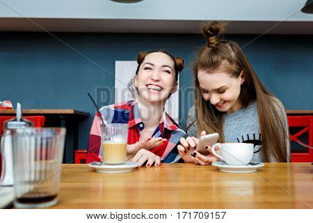 two young beautiful hipster women sitting at cafe, stylish trendy outfit, europe vacation, street style, happy, having fun, smiling, sunglasses, looking at smartphone, taking selfie photo, flirty.