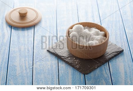 salt on black stone and wooden background