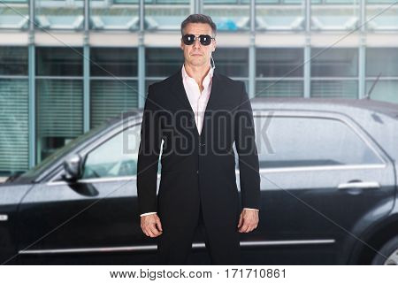 Portrait Of A Serious Male Security Guard Standing In Front Of A Car