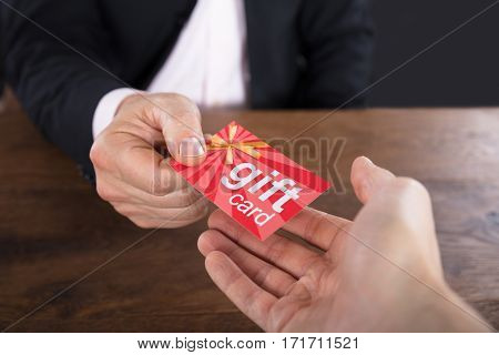 Close-up Of A Businessperson Hands Giving Gift Card To Other Businessperson
