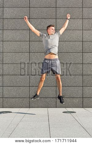 Full length of successful jogger jumping against tiled wall