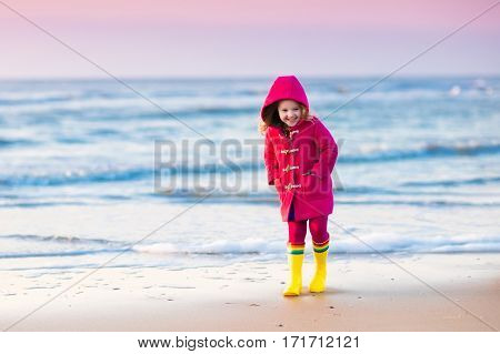 Happy little girl running and jumping in the waves on North Sea beach during winter vacation in Holland. Kids play in ocean sand dunes on cold autumn or spring day. Beach fun for family with children.