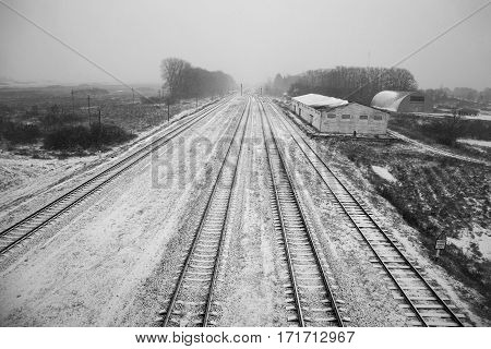 Belarus - November 2016 Long railroad tracks in the snow winter on the railroad farm sheds endless path top view view from the bridge black and white imageroad sign