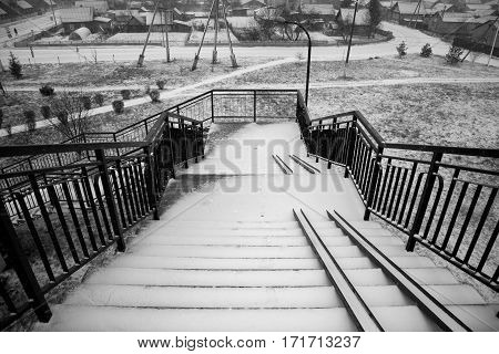 Belarus - November 2016 High stairs over the railroad tracks leading into the city the staircase in the snow steps in the snow stairs for baby carriages tracks paths shrubs alley street lights electricity poles