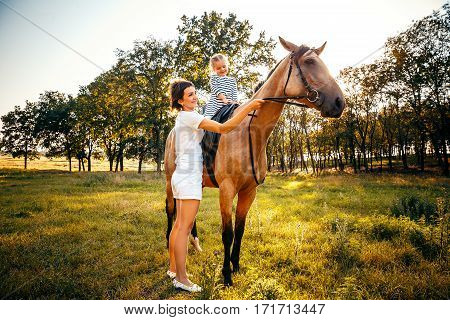 Little girl riding on a horseback with her mother standing nearby.