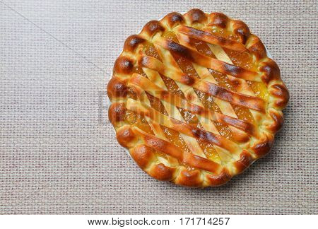 Delicious cake with apricot jam on sackcloth background