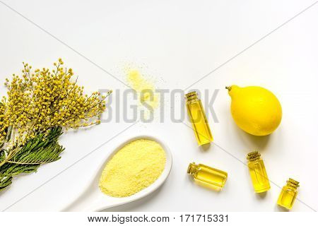 Yellow cosmetic sea salt with essential oils and fresh lemon on white background top view mock-up
