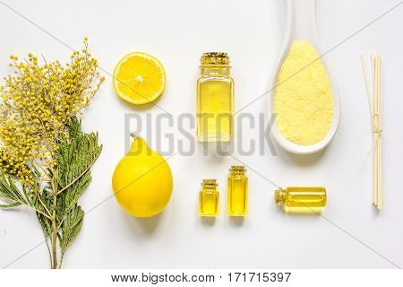 Yellow cosmetic spa set with aroma oils and bath salt on white table background top view