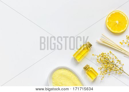 Yellow organic cosmetic set for body care with oil and sea salt on white background top view
