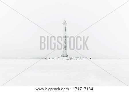 Foggy lighthouse in a calm and desolate winter landscape. A white old lighthouse isolated in mist.