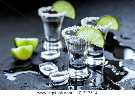 Alcohol party in bar with silver tequila, ice cubes and salt on black background