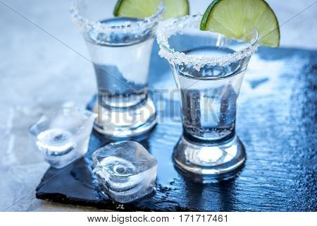 Silver tequila shots with fresh green lime and salt in bar on gray stone background