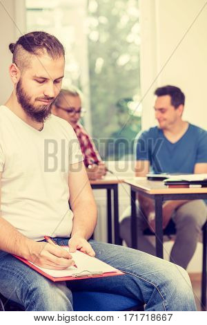 Education high school teamwork and people concept - student boy with notebook sitting in front of students her group mates in classroom