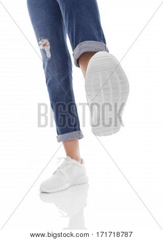 Female feet in sneakers want something to trample. Isolation on a white background.