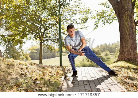 Full length of young man stretching on path in park