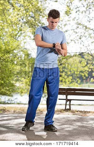 Full length of sporty man checking time on path in park
