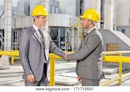 Two male architects shaking hands at construction site