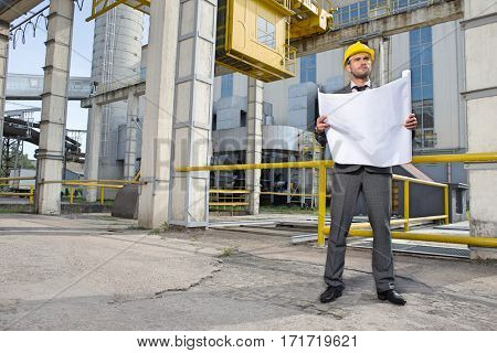 Full length of young male architect with blueprint outside industry