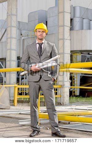 Portrait of confident young businessman holding rolled up blueprints outside industry