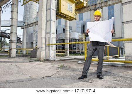 Full length of young male architect examining blueprint outside industry