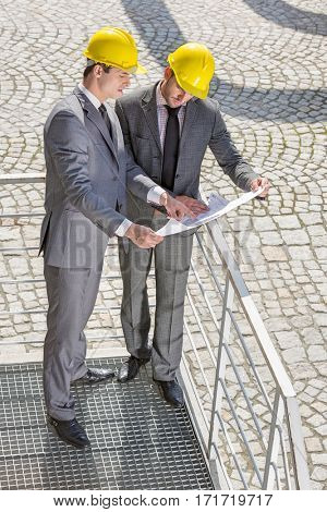 Full length of young male engineers discussing over blueprint on stairway