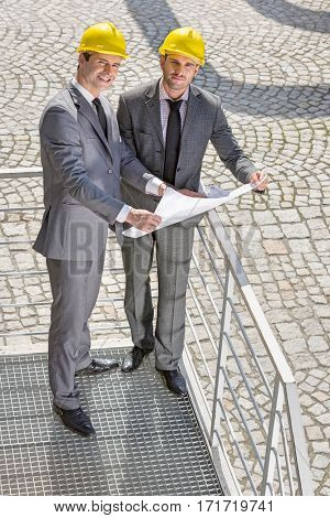 Full length portrait of young businessmen with blueprint on stairway